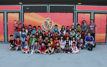 Elementary School students and staff at a J League soccer game.